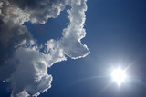 White clouds in the blue sky against the bright sun - 209930472