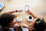 Mockup, friends browsing phone together at cafeteria - 209930481