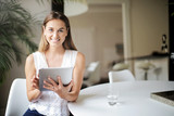 Smiling young woman holding a tablet - 209933299