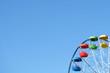 Multicolored Ferris wheel against the blue sky. Close-up.