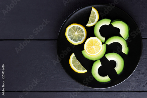 Foto Murales Avocado on a black plate top view, sliced avocado and lemon on black wooden boards, vegetarian food, useful natural food, tropical fruits for breakfast, Chilean food, copy space
