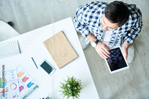 From above shot of casual man holding tablet and standing in modern creative office near table.