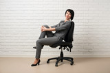 the business woman sitting on a chair, dressed in a gray suit poses in front of a white wall - 209941858