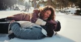 Young romantic couple lying down in snow and embracing - 209947882