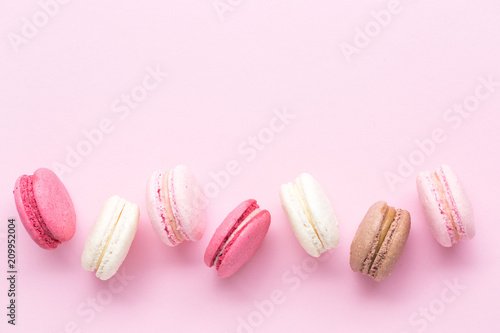 Fotobehang Macarons Colorful cake macaron or macaroon isolated over pastel pink background. Top view