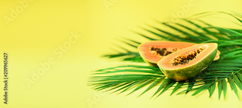Papaya fruit over tropical green palm leaves on yellow background. Top view with copy space. Pop art design, creative summer concept. Raw vegan food. Banner.