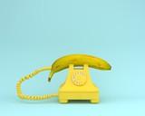 Fototapety Creative idea layout fresh banana with yellow retro telephone on bluish background.  Fruit minimal concept.