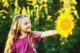 Cheerful girl holding a sunflower flower