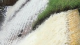 Water from a river flows down a manmade dam in slow motion in a rural region - 209979238