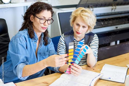 Dwa atrakcyjnej kobiety siedzi przy stołem w drukowym biurze i wybiera kolor od palety.