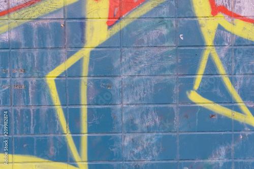 Yellow graffiti details on blue tiles wall