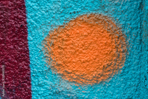 Orange and red graffiti details on a blue painted wall, facade. Abstract background, wallpaper.