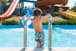 healthy small boy in shorts standing near summer blue swimming pool in water park