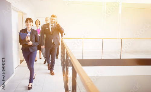 Wall mural Businesswoman Walking On Corridor With Colleagues By Railing In Office