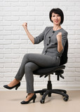 the business woman sitting on a chair, dressed in a gray suit poses in front of a white wall - 209986634