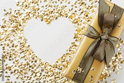 Gift or present box and golden sequins heart on table top view. Flat lay composition for Christmas or birthday.