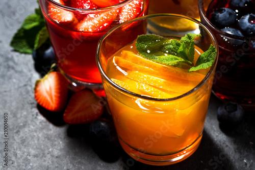 Foto Murales fresh fruit lemonades in assortment on dark table, top view closeup