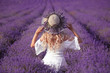 Quadro back view of Young blond woman in lavender field. Happy carefree female in a white dress and straw hat enjoying sunset. Outdoors portrait.