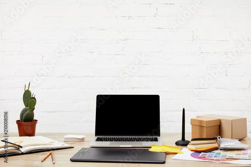 bliska widok laptopa, tablet graficzny, notebooki i palety na powierzchni drewnianych w miejscu pracy projektant graficzny