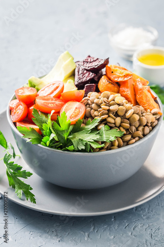 Buddha bowl with roasted root vegetables, greens, lentils, tomatoes. Selective focus, space for text. - 210008272