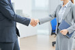 Business colleagues shaking hands while standing at office - 210011678