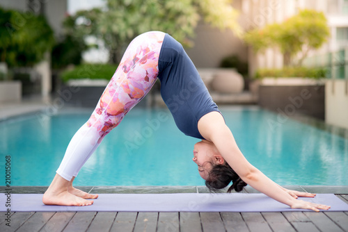 Plakat young Asian woman doing yoga exercise with downward facing dog posing