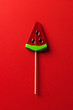top view of lollipop in shape of watermelon on red surface with water drops