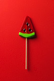 top view of lollipop in shape of watermelon on red surface with water drops - 210019205