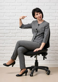 the business woman sitting on a chair, dressed in a gray suit poses in front of a white wall - 210026014