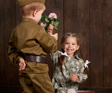 children boy are dressed as soldier in retro military uniforms and girl in pink dress sitting on old suitcase, dark wood background, retro style - 210026482