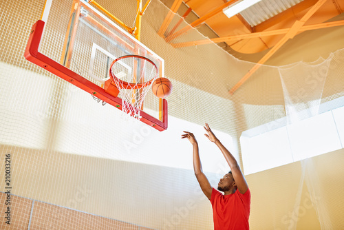 African-American man in red T-shirt trying to shoot goal while playing basketball in gym.