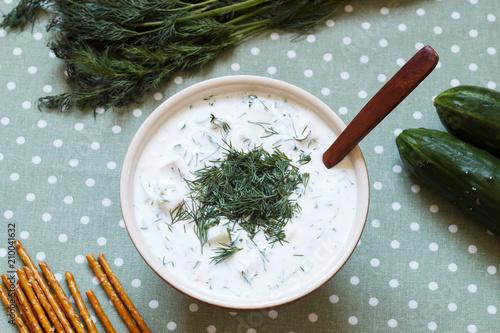 Foto Murales Okroshka. Traditional cold soup of cucumbers, onions, dill, fresh herbs and yogurt. Top view.