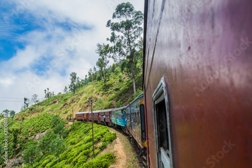Fotobehang Bruin IDALGASHINNA, SRI LANKA - JULY 16, 2016: Local train rides near Idalgashinna village. Locals hang out of doors.