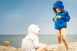 two little cute girls playing on the sand at the beach in summer
