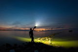 A young man staying on the stone breakwater line and holding very powerful torch. - 210050858