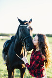 Black horse kissed by a young woman. - 210051406