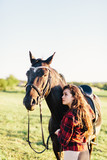 Young girl hugging purebred black horse on the field. - 210051623