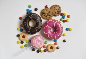 Close up of dessert with candy, chocolate and strawberry donuts and fruitcake on white background