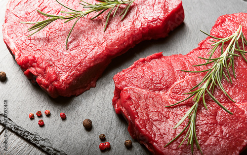 two pieces of fresh meat on a wooden table - 210053448