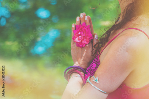 Plakat close up of yoga woman hands in namaste gesture with rose flower outdoor