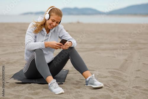 Fotobehang Muziek Young sports woman listens to music on the beach
