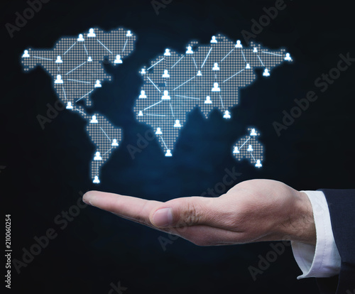 Foto Murales  Businessman holding people symbols with world map. Global business communication concept.