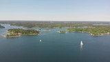 Droneview of two sailboats sailing in opposite directions in the Swedish archipelago, filled with blue waters and islands with houses on. - 210066478
