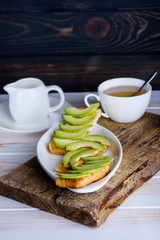 Breakfast with sandwich from avocado and fragrant tea