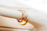 Golden wedding rings on bride shoes with rhinestones. Wedding jewelry details. Symbol of love and marriage.