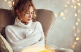 Woman with warm mug sitting in armchair - 210088637