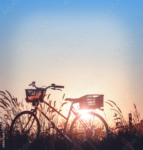 Aluminium Fiets beautiful landscape image with Bicycle at sunset on glass field meadow ; summer or spring season background