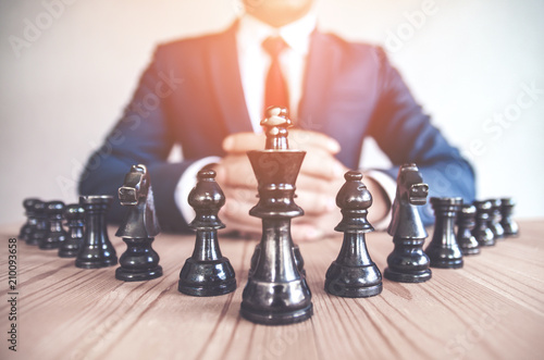 Poster Retro style image of a businessman with clasped hands planning strategy with chess figures on an old wooden table.