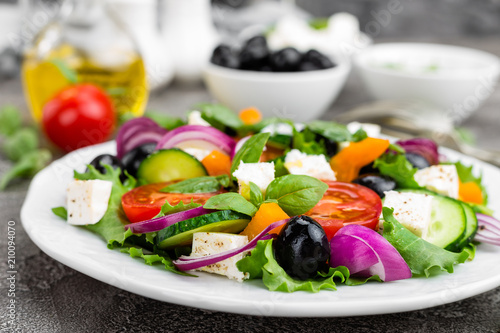 Greek salad. Fresh vegetable salad with tomato, onion, cucumbers, pepper, olives, lettuce and feta cheese. Greek salad on plate - 210094070