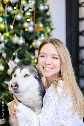 Foto Murales Portrait of smiling girl with husky, decorated fir tree in background.Concept of celebrating Christmas and New Year, pets and winter holidays.